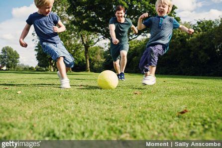Groupe d'enfants qui jouent au ballon de foot dans le jardin