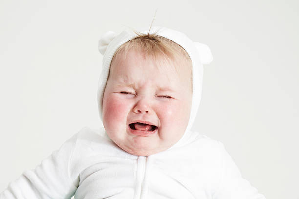 Bébé avec cagoule ours blanche en train de pleurer