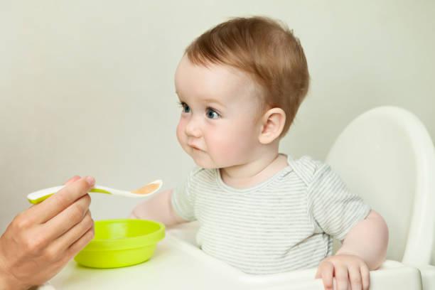 Bébé l'air étonné en train de manger son repas sur une chaise haute
