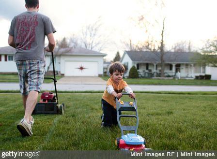 Un papa et son fils qui tondent la pelouse de leur jardin